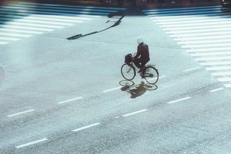 union familiar: Desenfoque de movimiento y silueta de hombre montar en bicicleta a través de la calle en el cruce de Shibuya, Tokio, Japón. El cruce más famoso y la gente grande de la corona señalan en Tokio.