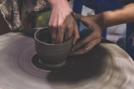 Professional Thai man using mechanic pottery make mug, earthenware at Night Plaza Market in Thailand. Reklamní fotografie