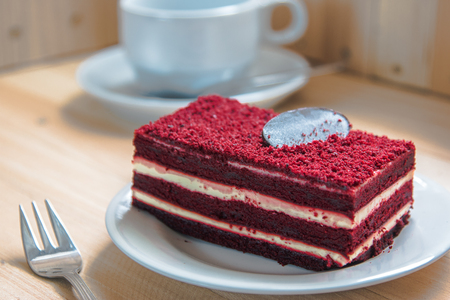 Red velvet cheese cake topping by dark chocolate on white plate put on wooden table.