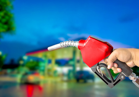 Fuel nozzle red on the bokeh background. Drive economy Travel investment Фото со стока