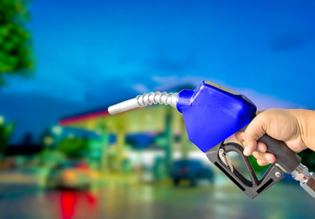 Fuel nozzle red on the bokeh background. Drive economy Travel investment Stock Photo