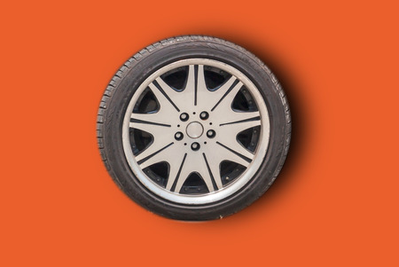 Car wheels on a white background behind a cutting machine separa