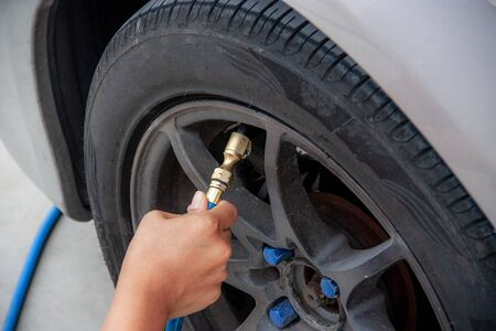 Woman's hands fill the car tire with a simple matter.
