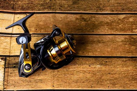 New technology fishing reel on wooden floor