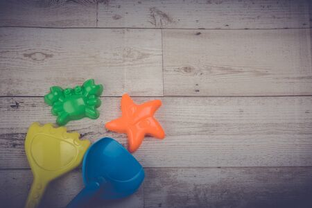 Crab, starfish, scoop, sand, rake, toy on wooden floor, holiday concept