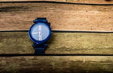 steel clock on wooden background.