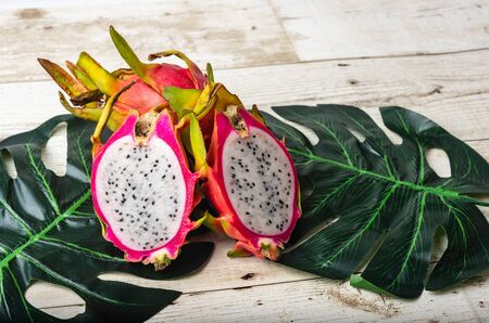 Dragon fruit or pitaya with slice isolated on ornamental leaf background, exotic tropical diet nutrition Food
