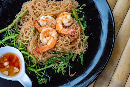 Stir-fried shrimp with vermicelli on a plate of Asian street food