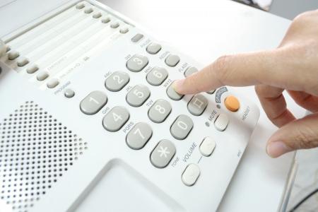 Finger pressing key on phone