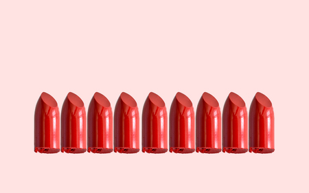 red lipstick bullet on pink pastel color background with copy space for promotion or advertising