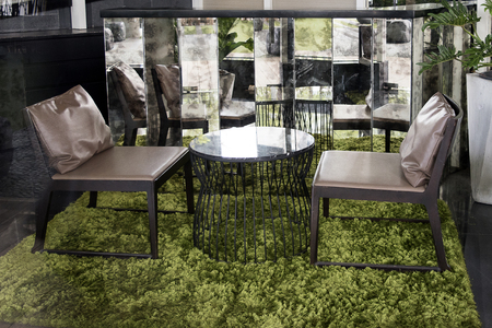 Modern furniture having brown leather chair and marble table on green grass carpet at the coffee shop Banque d'images - 106642214