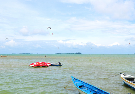 boat on the sea with parasail in the background on cloudy sky