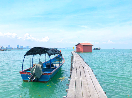 Wooden bridge at Clan Tan Jetty on a cloudy day with blue sky and fisherman boat