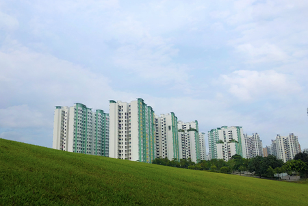 Modern Looking residential apartment (HDB) in Singapore near open field hill under cloudy blue sky