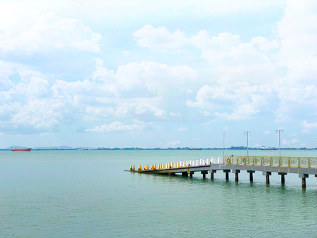 Pier under cloudy blue sky with boats at the background