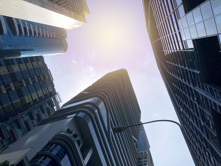 Worms-eye view of Singapore CBD buildings with the sun Editorial