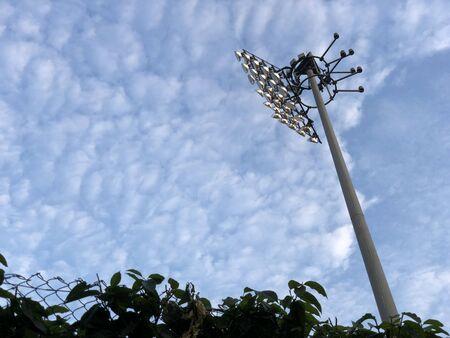 Sport stadium spotlight with cloudy blue sky background.