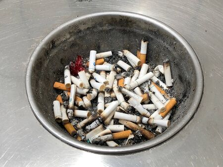 Focus/ macro view of cigarette buds on an ash tray atop the rubbish bin