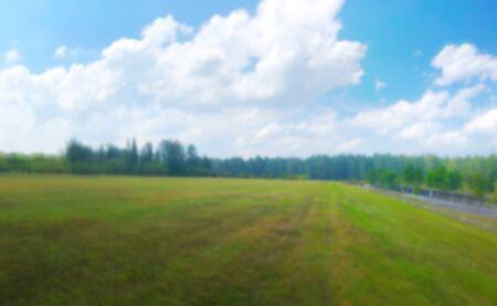 Green field under cloudy blue sky