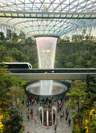 Singapore: 13 April 2019 - Waterfall at Jewel Changi Airport, Singapore. Named the Rain Vortex, it is the tallest indoor waterfall, which is surrounded by a terraced forest setting.