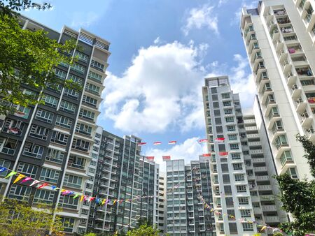 Many Singapore National and Community flags are attached high up with strings above the residential apartments to celebrate the National Day. Stock Photo
