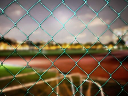Chain link fence with blurred stadium as background
