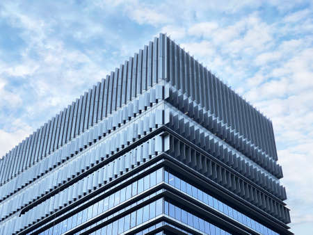 Modern looking commercial building exterior under cloudy blue sky