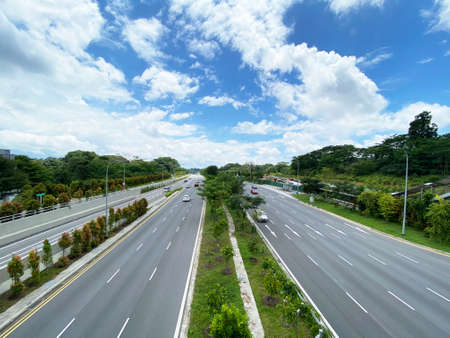 Street view with two way traffic around nature park from overhead pedestrian bridges Stock Photo