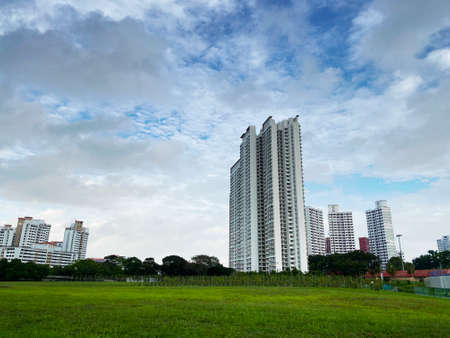 Distant view of residential apartment (HDB) with empty field under cloudy sky