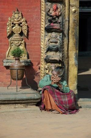 Bhaktapur,Nepal,December 29,2007 - Old poor woman sitting near entrance to hindu temple in Bhaktapur.Bhaktapur is one of the most popular landmarks in Asia, receiving millions of visitors annually