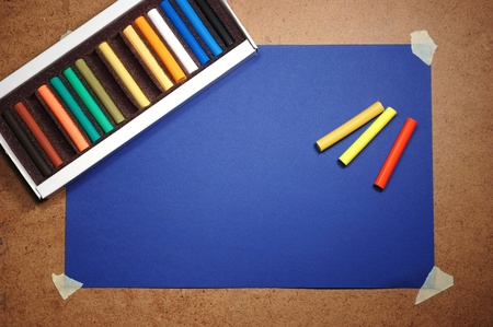 Empty blue cardboard background and multicolored pastel - art utensil photo
