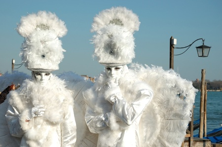Venice,Italy, March 8,2011-Two masks -white angels at St. Mark's Square during the Carnival of Venice on March 8, 2011.The annual carnival was held in 2011 from February 26th to March 8th Stock Photo - 9205266
