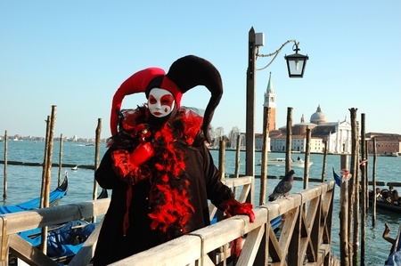 Venice,Italy, March 8,2011- Person in Harlequin mask near canal during the Carnival of Venice.The annual carnival was held in 2011 from February 26th to March 8th. Stock Photo - 9218331