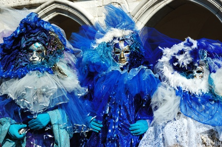 Venice,Italy, March 8,2011- Three masks dressed in blue costumes at St. Mark's Square during the Carnival of Venice .The annual carnival was held in 2011 from February 26th to March 8th Stock Photo - 9309015