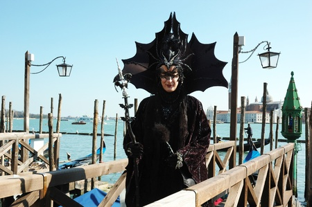 Venice,Italy, March 8,2011-Lady dressed in costume of black bat near canal during the Carnival of Venice.The annual carnival was held in 2011 from February 26th to March 8th. Stock Photo - 9309013