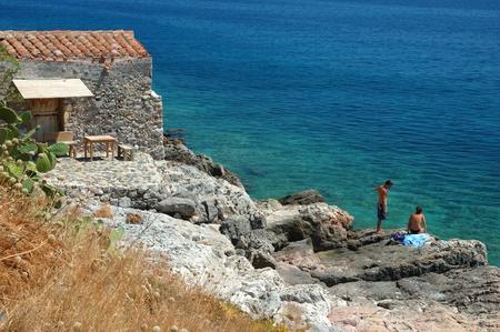 Monimvasio,Greece, August 10, 2011- Public beach at Monimvasio -  popular tourist place in Aegean sea.Town daily receives thousands of tourists