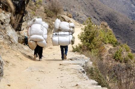strong base: Due portatori sherpa che trasportano sacchi pesanti in Himalaya Everest Base Camp trek, Nepal sherpa sono alpinisti d'elite ed esperti nelle montagne dell'Himalaya Archivio Fotografico