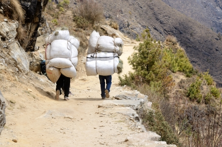 Two sherpa porters carrying heavy sacks in the Himalaya at Everest Base Camp trek ,Nepal Sherpas are elite mountaineers and experts in the Himalaya mountains