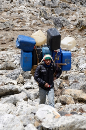 sherpa: Everest region,Nepal,April 21,2013 - sherpa porter carry heavy load in the Himalaya at Everest Base Camp trek Sherpas are elite mountaineers and experts in the Himalaya mountains   Editorial
