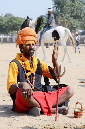 ascetic: Pushkar,India,November 12,2013 - Sadhu,holy man perform at annual camel fair in Pushkar,Rajasthan,India In Hinduism, sadhu is a common term for an ascetic or someone who practices yoga  yogin