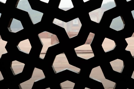 mughal empire: Traditional islamic ornament period of mughal empire  with swastika at sandstone grill on medieval window,Humayun Stock Photo