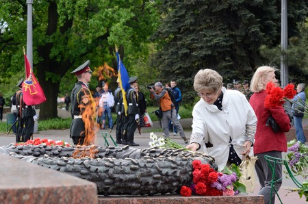 commemoration: Odessa,Ukraine,May 9,2014 - Old lady put flowers to Eternal Flame in commemoration of Soviet soldiers who fought against Nazi invasion during Second World War in Odessa,Odessa,Ukraine Editorial