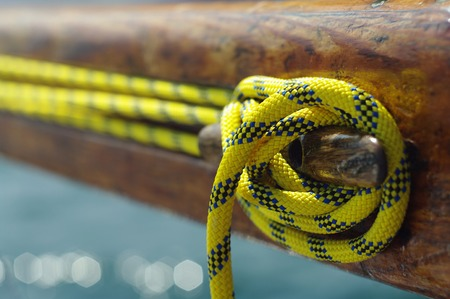 Closeup of old vintage snatch cleat with yellow line on wooden yacht, tool for keeping ropes tightened  photo