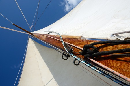 snatch: Old wooden mast with crosspieces, backstays,mainsail and staysail, view from deck of boat Stock Photo