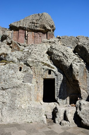 geghard: Cross-stones and entrance to monastic cells of Geghard rock monastery
