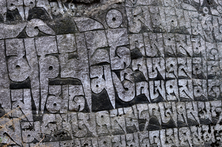 samsara: Ancient buddhist carved stone wall with sacred religious mantras written in tibetan language,Eastern Nepal, Everest region,Asia Stock Photo