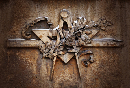 freemasonry: Grunge freemasonry emblem on dramatic background - masonic square and compass symbol, closeup of old architectural building decoration