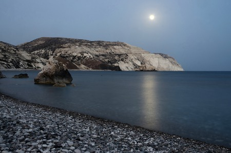 pebblestone: Night seascape of Aphrodites Rocks beach with moon shine, bithplace of greek  goddess of love, Paphos, Western Cyprus, also called Petra tou Romiou, famous landmark Stock Photo
