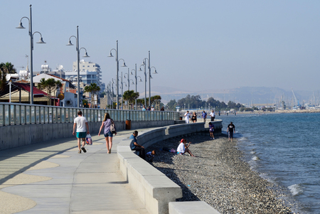 eponymous: LARNACA, CYPRUS - APRIL 7, 2016: view of Larnaca seafront with palm trees , pedestrians and beach on April 7 in Larnaca, Cyprus.Larnaca -  is a city on  southern coast  and capital of eponymous district.