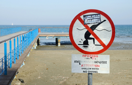 eponymous: LARNACA, CYPRUS - APRIL 7, 2016: view of Larnaca Phinikoudes beach with red no jumping warning sign on April 7 in Larnaca, Cyprus.Larnaca -  is a city on  southern coast  and capital of eponymous district.